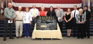 Family members of the RAIDR 21 crew stand behind a plaque created in memory of their loved ones during a remembrance ceremony on Barksdale Air Force Base, La., July 21, 2013. The plaque lists the names of the crew: Col. George Martin, Maj. Christopher Cooper, Maj. Brent Williams, Capt. Michael Dodson, and First Lieutenants Robert Gerren and Joshua Sheperd.