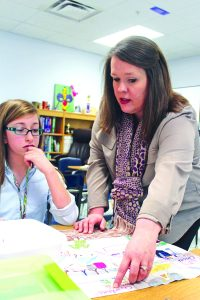Benton Middle School teacher Amanda Eagle assists sixth grader Carlee Smith with a classroom assignment.