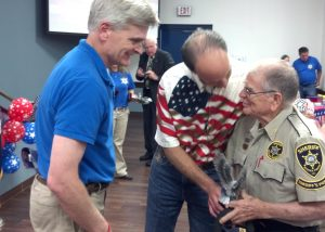 "Bossier Sheriff Julian Whittington (center) and U.S. Representative Bill Cassidy present BSO Posse member and WWII veteran Bill Breeland with a special award for his military service. The presentation was held as part of the 4th of July ""In God We Trust"" rally Friday, and Breeland was one of six posse members honored  during the event for their service in WWII."
