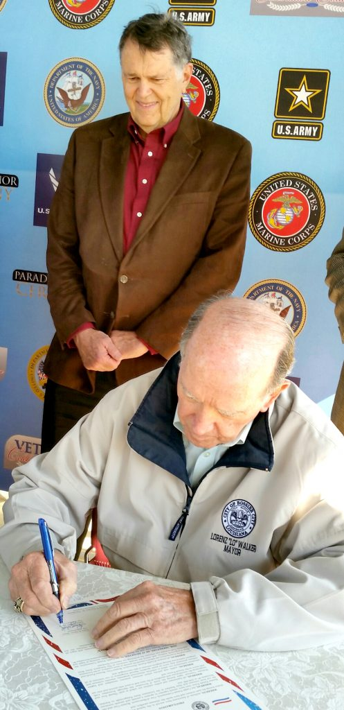 "(photo by Tom Pace) Bossier City Mayor Lorenz ""Lo"" Walker signs the declaration to name Nov. 5-11 as Veterans Celebration Week while Bossier Parish Police Jury President Doug Rimmer looks on."