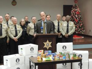 Sheriff Julian Whittington speaks at a press conference before deputies distribute Operation Blessing food boxes to local residents.