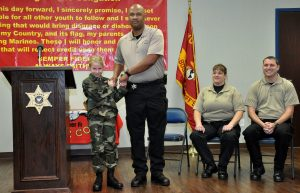 Commander Lavaro Ramey presents the Physical Fitness Award to 8-year-old Destiney Buckner.