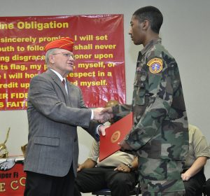 Lt. Col. Mike Thornton, USMC (Ret.), presents Frederick Jones, Jr., 14, with the Floyd L. Baxter Leadership Award from the Red River Detachment of the Marine Corps League.