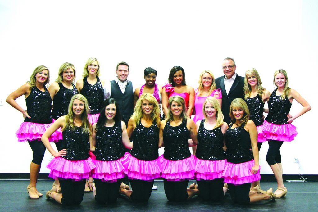 Participants for the Dancing for the Cure event from Vicki's School of Dance pose with Doug Warner during practice for the event.