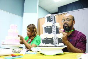 Amanda Simmons/Press-Tribune | Demetrus and Niecey Wesley, Bossier City residents and owners of Sooo Good Bakery in Shreveport, work on their royal icing piping skills at a class taught by international cake artist Ceri DD Griffiths, owner of Ceri Dz Artistry & Design Ltd. in Great Britain.
