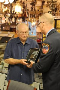 Amanda Simmons/Press-Tribune | Retired NYC firefighter John Turkus (right) presents John Henson, owner of Henson Carpet One Floor & Home, with a commemorative shadow box on behalf of the Stephen Siller Tunnel to Towers Foundation, named for a FDNY firefighter who died trying to save people at the World Trade Center on Sept. 11, 2001. The Building for America's Bravest Shadowbox Tour is a thank you to Carpet One members across the country for their dedication and donations.