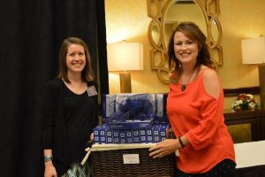 Courtesy Photo | Melissa Couch presents new teacher Katie Chavis with 25 7' inch tablets for use in her classroom.