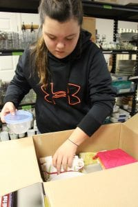 Amanda Simmons/Press-Tribune | Kayla Lynch, an eighth grader at Benton Middle School, packs a box of donated kitchen items at the Renesting Project, Inc. in Bossier City. The items will be used to create a home for a local couple who is transitioning out of homelessness.