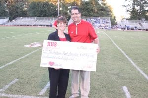 Guin presents a check to the American Heart Association in 2014 of proceeds from the Red Out for Rodney t-shirt sales & donations.