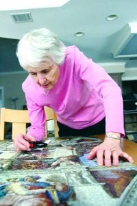 Amanda Simmons/Press-Tribune | Elizabeth Curran of Bossier City used a magnifying glass to view the details of the 5,000 piece Ravensburger puzzle she spent eight month assembling on her kitchen table.
